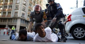 Riot policemen detain two men during a protest against the 2014 World Cup in Porto Alegre