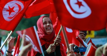 TUNIS, TUNISIA - FEBRUARY 8: Tunisians attend with Tunisian flags to the celebrations of Tunisian new constitution, organized by Ennahda Movement Party, outside the National Constituent Assembly building, on February 8, 2014 in Tunis, Tunisia. (Photo by Amine Landoulsi/Anadolu Agency/Getty Images)
