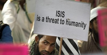 An Indian Muslim man holds a banner during a protest against ISIS, an Islamic State group, and Friday's Paris attacks, in New Delhi, India, Wednesday, Nov. 18, 2015. Multiple attacks across Paris on Friday night have left more than one hundred dead and many more injured. (AP Photo/Manish Swarup)